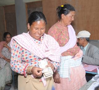 An older woman receiving her cash transfer. (c) Sachin Shrestha/HelpAge International
