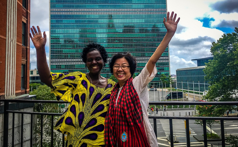 Older women Vanda and Vérène stand outside the United Nations in New York