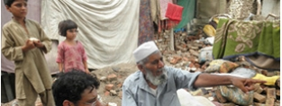 An older man and his family survey the wreckage caused by the floods in Pakistan. (c) HelpAge International/Ahmed Sohail.