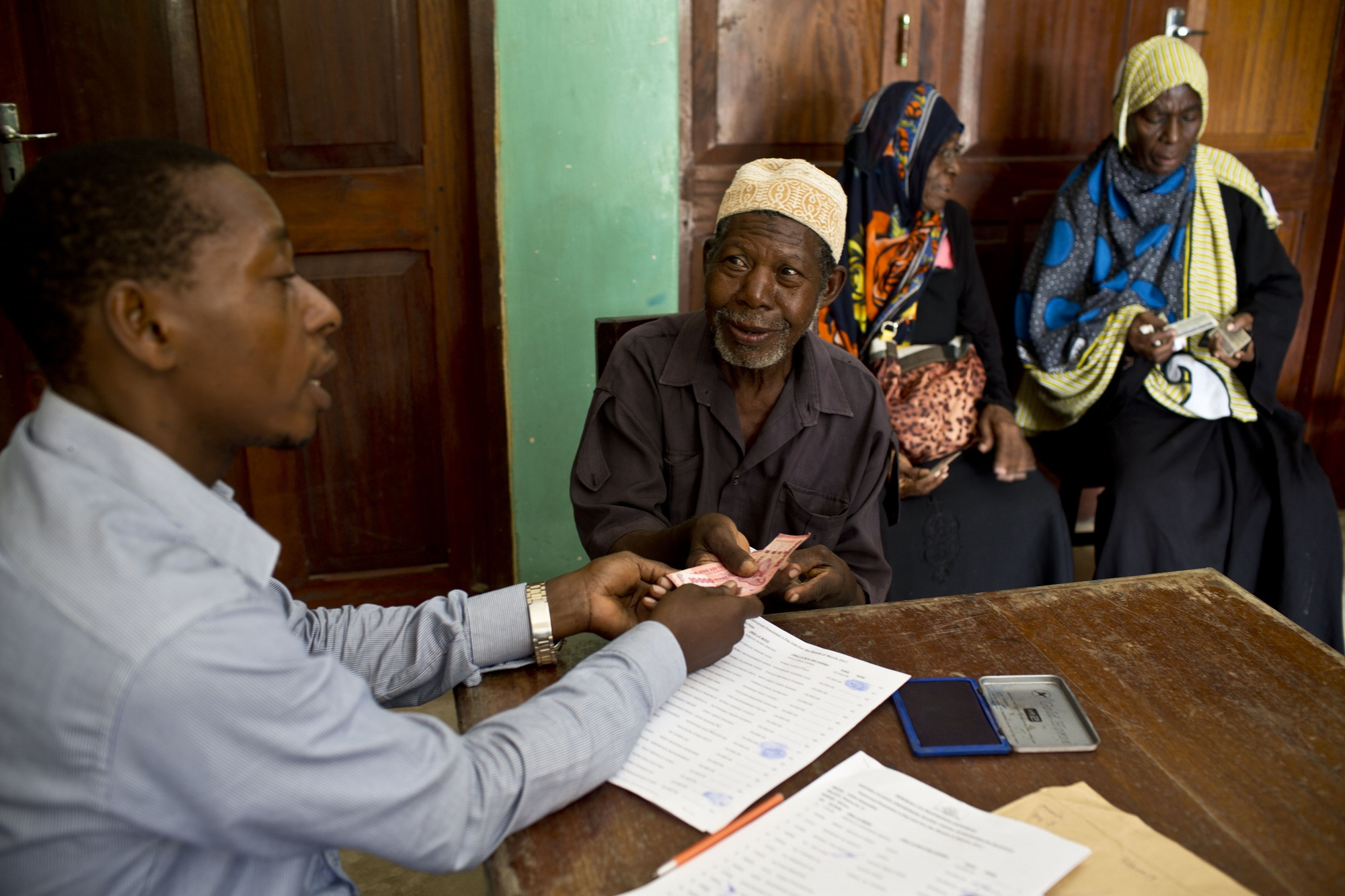 An older man collects a cash transfer in Tanzania (c) Kate Holt/Age International
