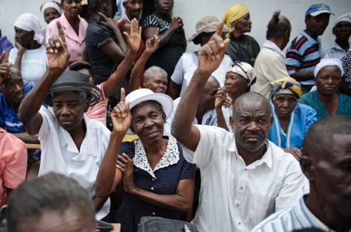 Older people in Haiti raised their hands to be counted.