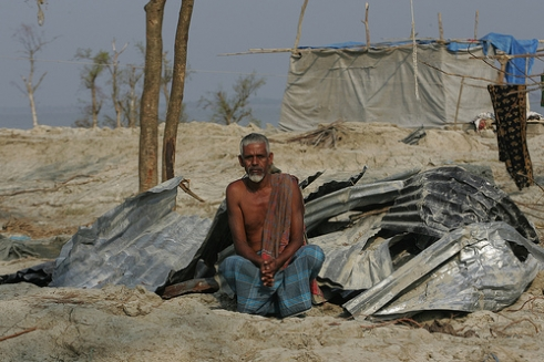 A Bangladeshi man outside his ruined home