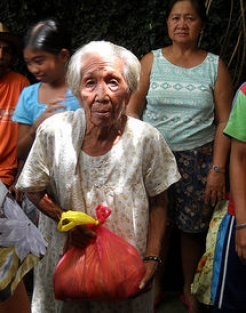 An older woman in the Philippines receives her relief package.