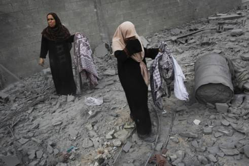 Palestinian women gather belongings from the rubble of a building in the northern Gaza Strip.