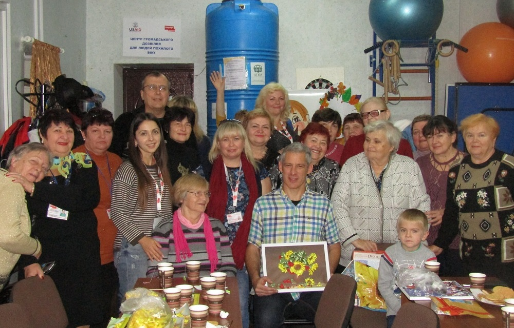 HelpAge International's Patrick Wilson with older people in a community safe space in Ukraine