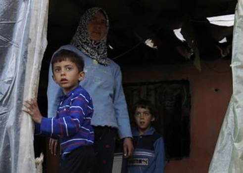 An older woman with her two grandchildren. She has fled Syria and is now living in a garage in Lebanon.