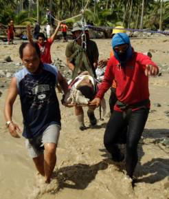 Rescue teams evacuate an older man from the devastation left by Typhoon Bopha.