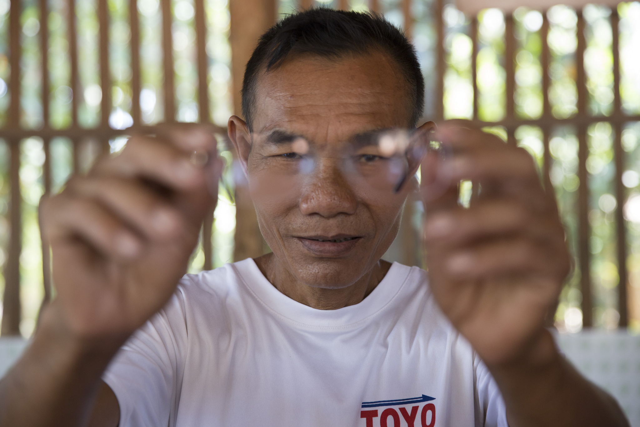U Mg Tay was provided glasses in Myanmar and is able to read again (c) Hereward Holland/Age International