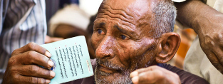 An older man waits to receive an identity card (c) Wolfgang Gressmann/Oxfam, March 2012 via Flickr