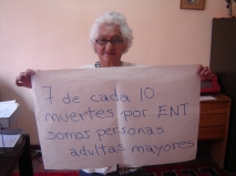 Older Bolivian woman holds sign saying '7 out of 10 deaths from NCDs are older people'